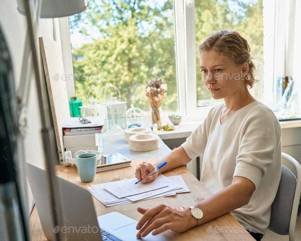 Young female entrepreneur designer writing on paper sheet, serious woman thinking and planning - Stock Photo - Images
