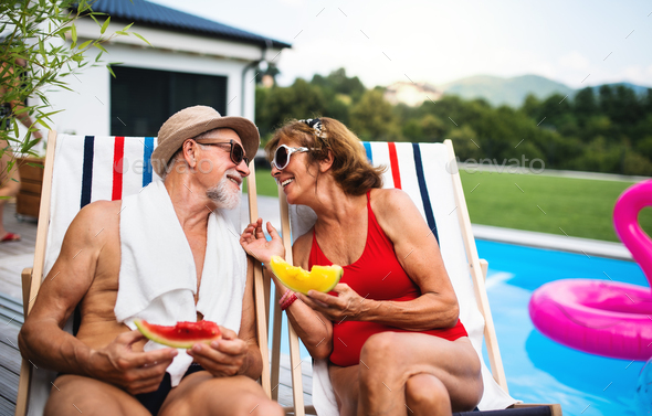 Cheerful senior couple sitting by swimming pool outdoors in backyard - Stock Photo - Images