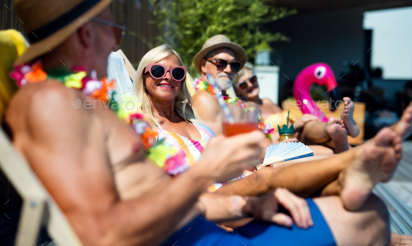 Group of cheerful seniors sitting by swimming pool outdoors in backyard, party concept - Stock Photo - Images