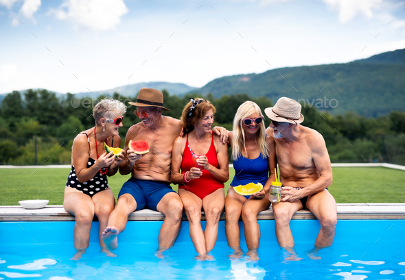 Group of cheerful seniors sitting by swimming pool outdoors in backyard - Stock Photo - Images