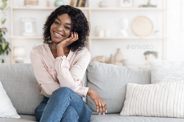 Home Portrait Of Beautiful African American Woman Posing On Couch In Stylish Interior, Free Space
