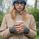 woman in autumnal casual clothes standing alone, looking down, holding in hands paper cup of coffee - PhotoDune Item for Sale