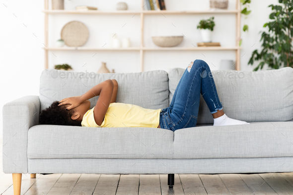 Teen's Depression. Frustrated Black Girl Crying Covering Face Lying On Couch At Home.