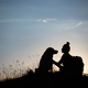 Woman with her dog sitting on the hill in the sunset. - PhotoDune Item for Sale