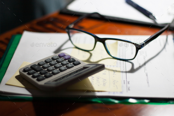 Glasses and calculator on a folder with documents, bills and notes on a desk - Stock Photo - Images