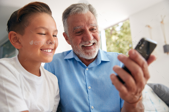 Hispanic Grandson Showing Grandfather How To Use Mobile Phone At Home - Stock Photo - Images