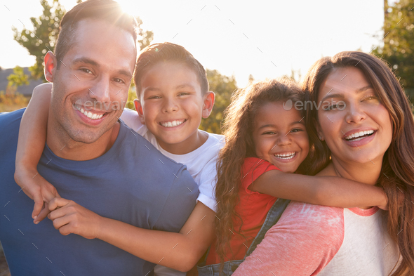 Portrait Of Hispanic Family Relaxing In Garden At Home With Parents Giving Children Piggybacks