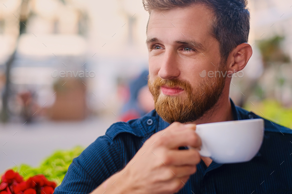 A man drinks coffee in a cafe on a street. - Stock Photo - Images