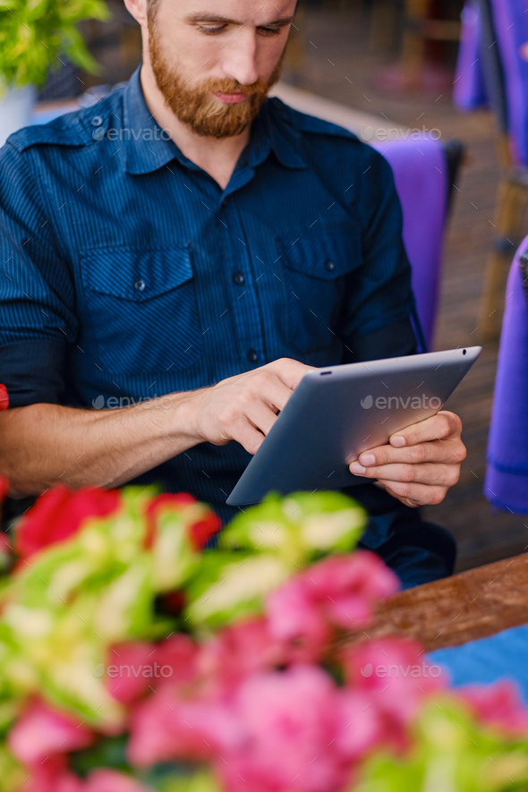 Redhead male using a tablet PC at the table. - Stock Photo - Images