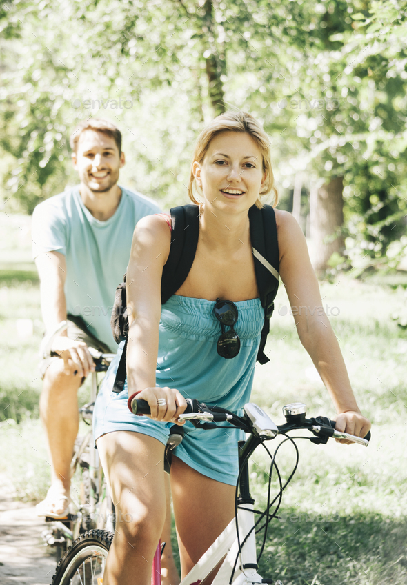 Young couple riding bicycle in park - Stock Photo - Images