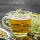 Tea of gray wormwood in glass cup with strainer on board - PhotoDune Item for Sale