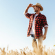 Image of unshaven adult man looking aside while standing at cereal field - PhotoDune Item for Sale