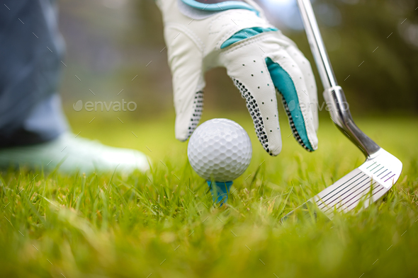 Hand in glove placing golf ball on tee - Stock Photo - Images