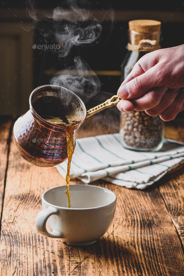 Pouring turkish coffee into white cup - Stock Photo - Images