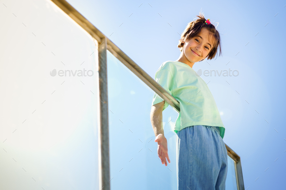 9-year-old girl posing happily on a staircase - Stock Photo - Images