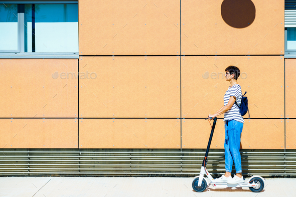 Woman riding around town on an electric scooter - Stock Photo - Images