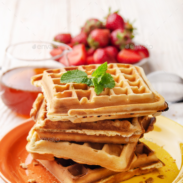 Pile of belgian waffles on white wooden kitchen table with strawberries and syrup aside - Stock Photo - Images