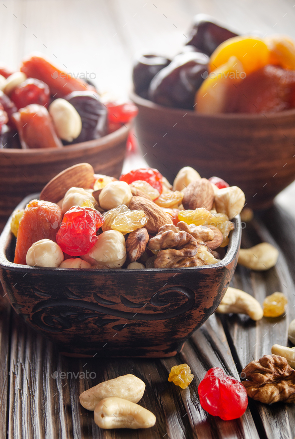 Assorted nuts and dried fruits in clay bowl on wooden kitchen table closeup - Stock Photo - Images