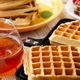Belgian waffles on cast skillet with stacked ones and syrup jug  aside - PhotoDune Item for Sale