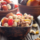 Assorted nuts and dried fruits in clay bowl on wooden kitchen table closeup - PhotoDune Item for Sale