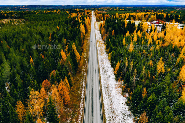 Aerial view of rural road with first snow in yellow and orange autumn forest - Stock Photo - Images