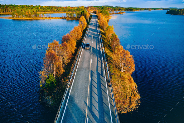 Aerial view of road and forest in autumn colors with blue water lake. - Stock Photo - Images