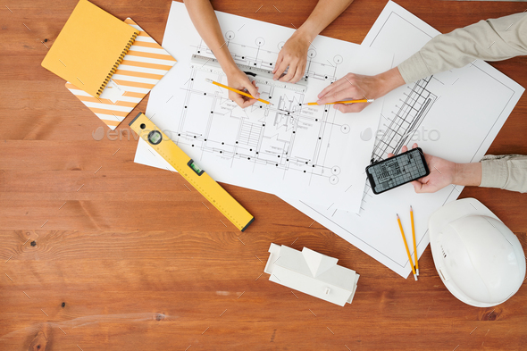 Top view of hands of two architects pointing at blueprint during discussion - Stock Photo - Images