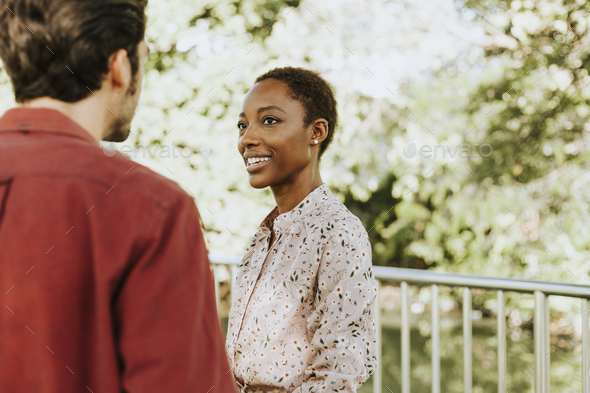 Man talking to a black lady in a park - Stock Photo - Images