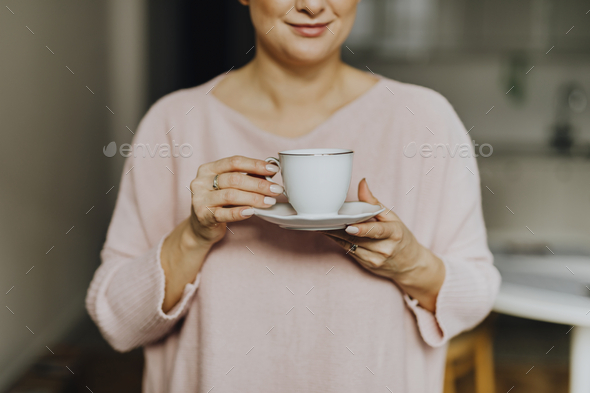 Happy woman enjoying a warm cup of tea for breakfast - Stock Photo - Images