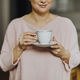 Happy woman enjoying a warm cup of tea for breakfast - PhotoDune Item for Sale