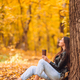 Fall concept - beautiful woman drinking coffee in autumn park under fall foliage - PhotoDune Item for Sale