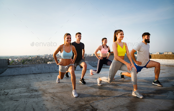 Group of cheerful fit fitness team exercising together outdoor to stay healthy