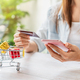Young woman holding a credit card and using smartphone for making online payment shopping - PhotoDune Item for Sale