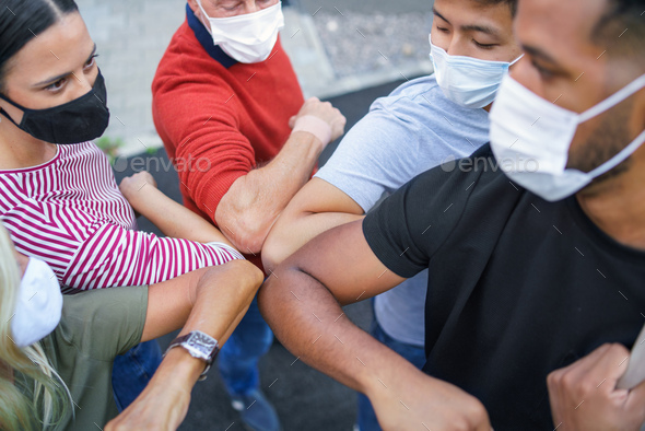 Group of people with face masks elbow bumping, coronavirus, covid-19 concept - Stock Photo - Images
