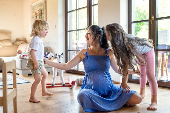 Pregnant woman with small children indoors at home, playing - Stock Photo - Images