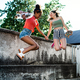 Young teenager girls friends with skateboards outdoors in city, jumping - PhotoDune Item for Sale