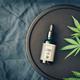 Medical marijuana cannabis products CBD oil and hemp leaves on dark background - PhotoDune Item for Sale