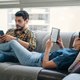 Couple Reading Ebook With Ereader On Couch - PhotoDune Item for Sale