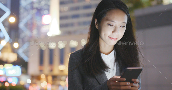 Woman use of cellphone in city at night - Stock Photo - Images