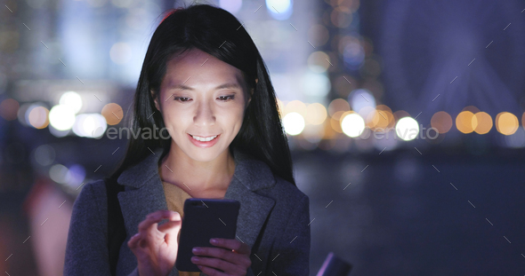 Woman look at mobile phone in city at night - Stock Photo - Images