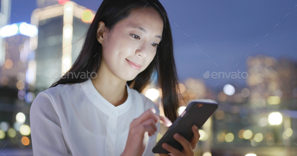 Asian Woman use of cellphone in city at night - Stock Photo - Images