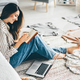 woman  writes in paper notebook sitting on floor near laptop at home. - PhotoDune Item for Sale