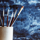 Painting brushes in a ceramic mug against a blue abstract background. - PhotoDune Item for Sale