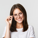 Close-up of smiling confident, beautiful brunette girl in glasses looking happy - PhotoDune Item for Sale