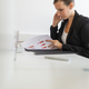 Profile view of young businesswoman sitting at her white office desk working - PhotoDune Item for Sale