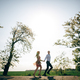 Beautiful young couple holding hands and running in sunshine in spring field and trees - PhotoDune Item for Sale
