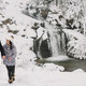 Happy romantic man and woman in luxury clothes gently kissing at waterfall in snow - PhotoDune Item for Sale