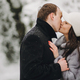 Portraits of happy romantic man and woman smiling and embracing at waterfall in snow - PhotoDune Item for Sale