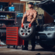 A man repairing wheel of a car. - PhotoDune Item for Sale