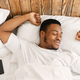 Rested African Guy Waking Stretching Hands Awakening In Cozy Bedroom - PhotoDune Item for Sale